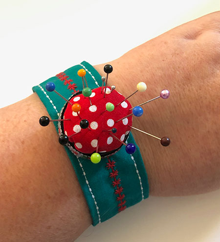 A pincushion on a strap to wear around your wrist
