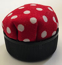 A pincushion made out of a bottle top.