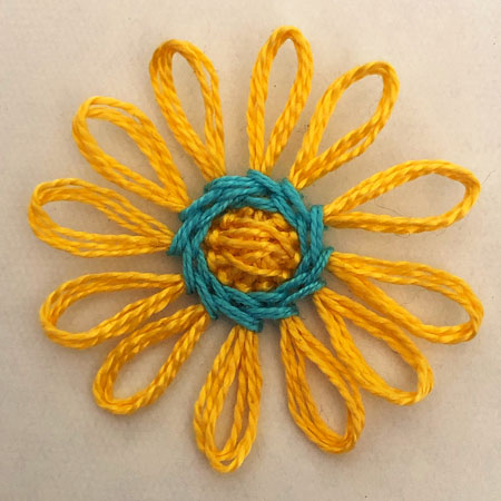 A daisy made from yellow thread with a stitched blue circle in the middle