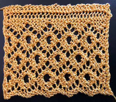 A knitted lace edging featuring lace diamonds with a large eyelet in the centre of each