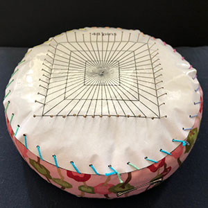 A teneriffe lace cushion with a paper plan sewn to the top