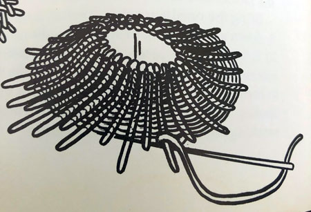 Black and white drawing of a mirror embroidered to a surface with padding behind it to create a raised, three dimensional form.