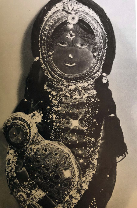 Black and white photo of a Madonna and Child, richly decorated with embroidery and small, round mirrors.