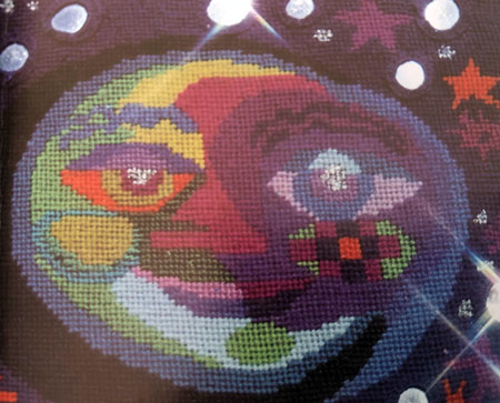 Needlepoint design showing the moon in flat areas of colour, with mirrors attached to represent stars.