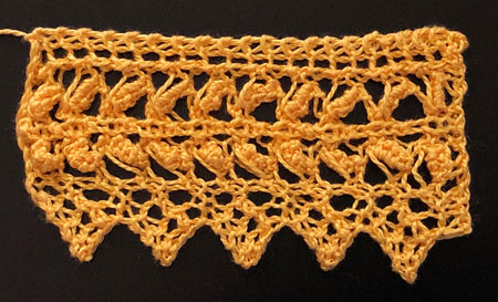 A yellow knitted lace edging with wide open bands of textured lace and a pointed edge