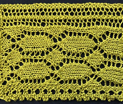 Knitted sample of lace for long curtains. Featuring lace lozenges and diamonds and a frilly border.