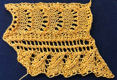 Knitted sample of a feather and fan lace with a leaf shaped edging.