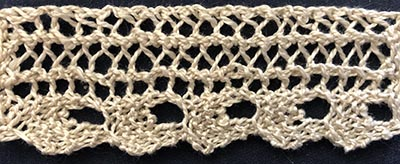 Knitted sample of a thin lace with a ric-rac shaped edging.