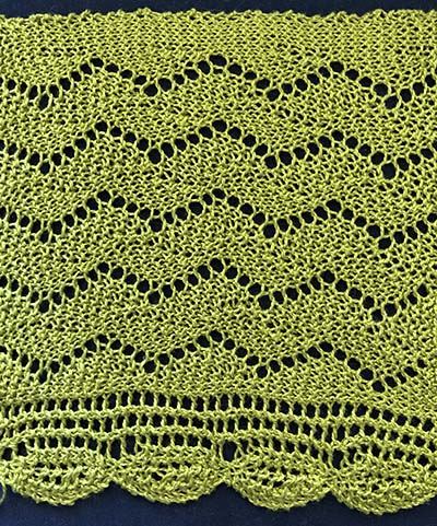 Knitted sample of a wide zig-zag lace border with knit in oval edging.