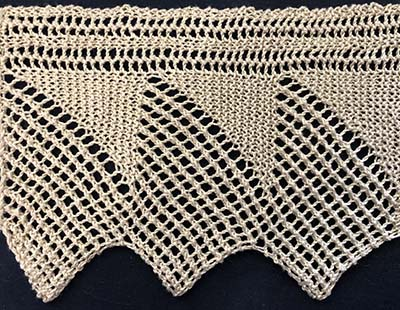 Wide knitted sample of a pointed lace edging.