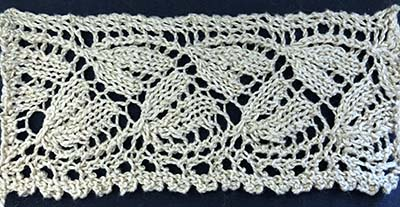 Knitted sample of wheat pattern edging with a band of floral motifs and frilly edge.