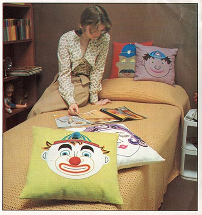 Four hand embroidered cushions with cartoon faces. 1974.
